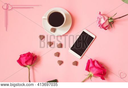 Cup Of Coffee, Heart Shape Chocolate Candies, Smartphone And Pink Roses. Top View, Copy Space.