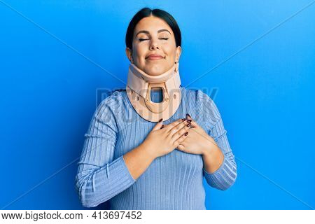 Beautiful brunette woman wearing cervical collar smiling with hands on chest with closed eyes and grateful gesture on face. health concept.