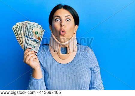 Beautiful brunette woman wearing cervical collar holding insurance money scared and amazed with open mouth for surprise, disbelief face