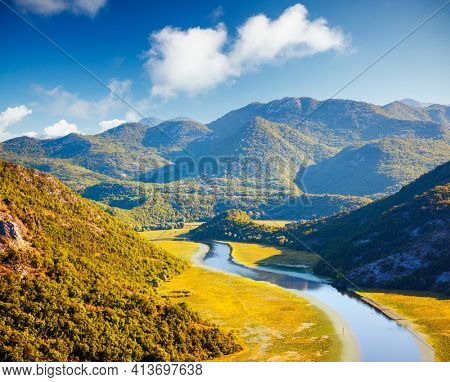 Picturesque view of the meander of the Rijeka Crnojevica on a sunny day. Location place National park Skadar Lake, Montenegro, Balkans, Europe. Vibrant photo wallpaper. Discover the beauty of earth.