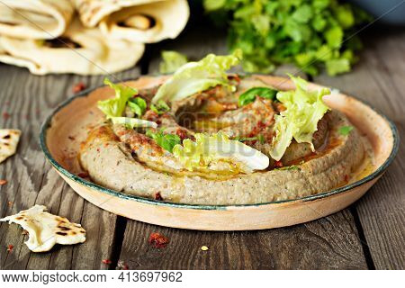 An Oriental Dish Of Baked Eggplant Babaganush (eggplant Puree) With Spices, Herbs, Lettuce And Orien