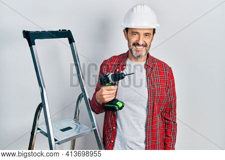 Middle age hispanic worker man holding screwdriver using ladder looking positive and happy standing and smiling with a confident smile showing teeth