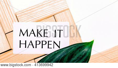 On A White Background Wooden Building Blocks, A White Card With The Text Make It Happen And A Green