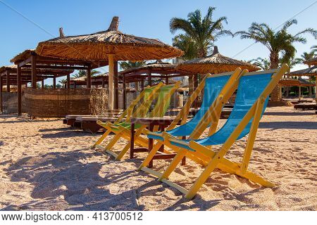 Four Sun Loungers And A Table On A Deserted Empty Beach, Sun Loungers And Umbrellas On The Shores Of