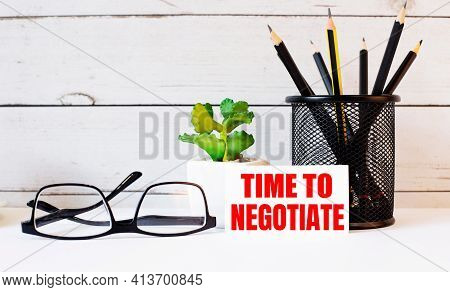 The Words Time To Negotiate Written On A White Business Card Next To Pencils In A Stand And Glasses.