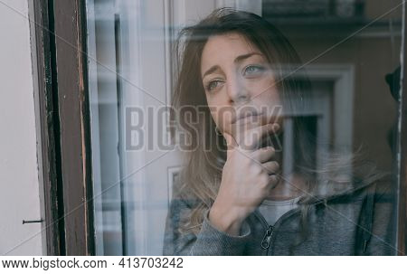 Young Attractive Unhappy Woman Suffering From Depression Looking Lost Through The Window At Home