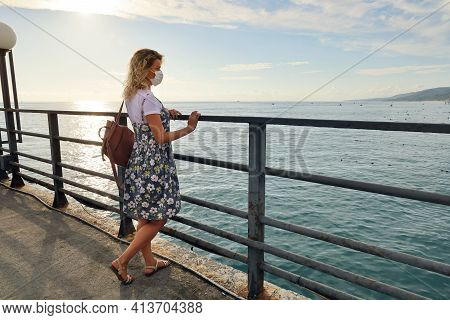 Young Woman In Summer Dress And Protective Mask On Her Face, Standing On Deserted Pier And Looks At