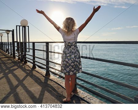 Young Woman In Summer Dress Stands Back With Raised Hands, On Deserted Pier On Background Of Sea And