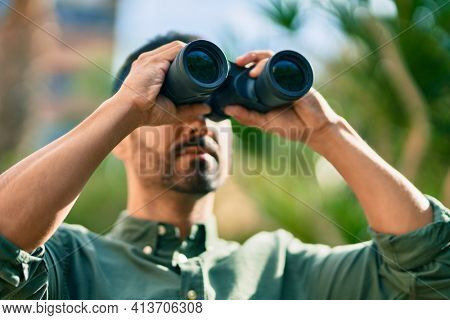 Young hispanic man smiling happy looking for new opportunity using binoculars at the park.