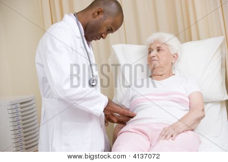 Doctor Giving Checkup To Woman In Exam Room