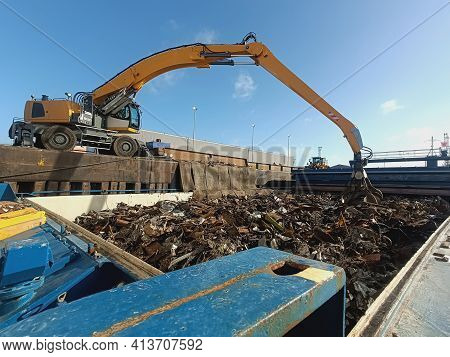The Grapple Loading And Unloading Crane Unloads Metal And Metal Waste For Recycling From The Ship's