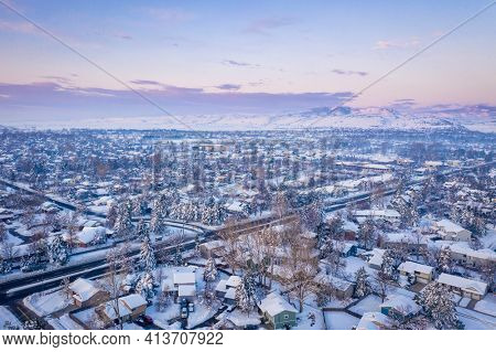 winter dawn over residential area of city of Fort Collins, Colorado, after heavy snowstorm - aerial view