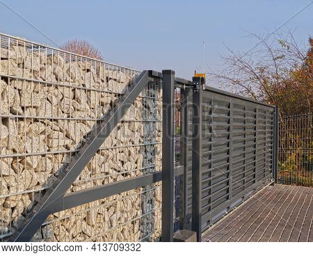 Automatic Entrance Gate Used In Combination With A Wall Made Of Gabion.