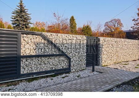Automatic Entrance Gate And Wicket Integrated Into The Wall Made Of A Gabion. A Fence Made Of Gabion
