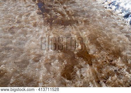 Slush, Puddles And Snow Porridge On The Road From Melting Snow During The Spring Thaw