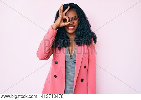Beautiful african woman wearing business jacket and glasses doing ok gesture with hand smiling, eye looking through fingers with happy face.