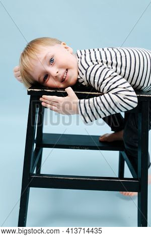Cute Blond Boy Lying On A Stepping Stool, Relaxing Over Blue Background