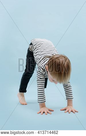 Flexible Blond Boy Stands On All Fours With Straight Legs. Over Blue Background