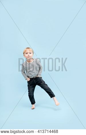 Amusing Blond Boy Standing On One Foot, Shifting His Weight. Over Blue