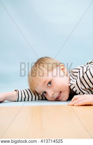 Handsome Blond Boy Lying On The Floor, Playing Cute. Over Blue Background