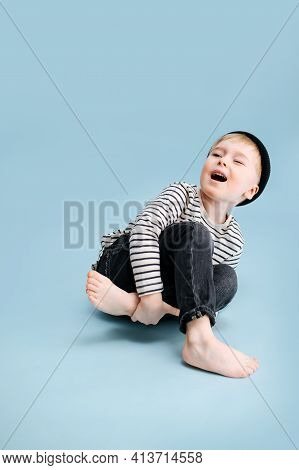 Acting Blond Boy Sitting On The Floor, Tilting To The Side, Holding His Leg