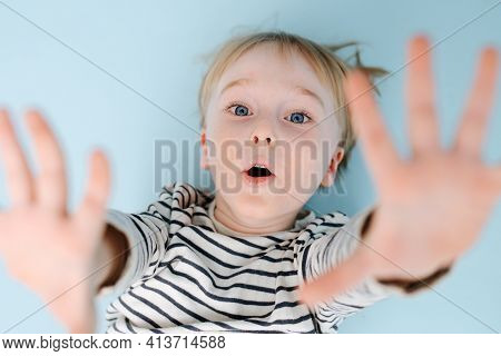Blond Boy Lying On The Floor With Wide Open Mouth. Over Blue Background.