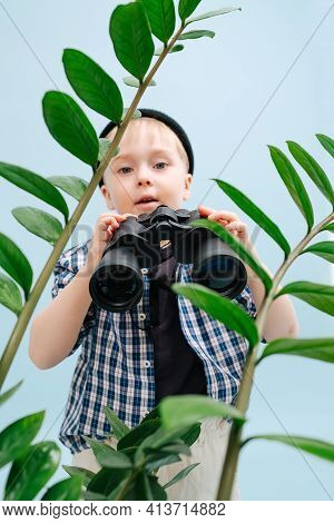 Nine Year Old Boy Standing Behind Plant Branches With Binoculars In His Hands
