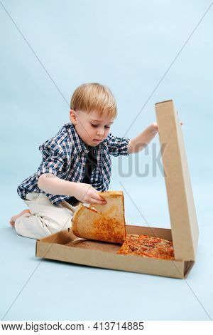 Hungry Little Blond Boy Sitting On The Floor, Tearing Pizza Slice For Himself