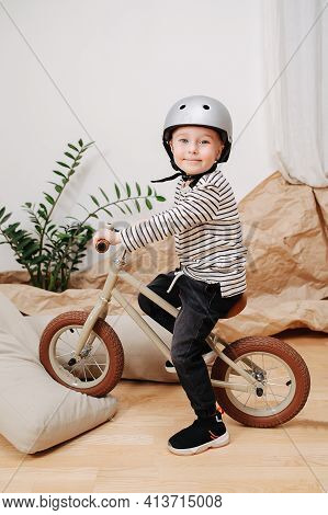 Fake-smiling Blond Boy Posing For A Photo On A Small Beige Two Wheel Bike