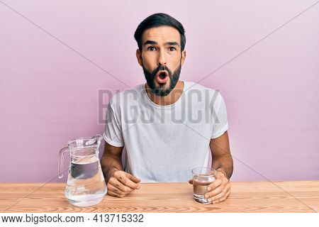Young hispanic man drinking glass of water sitting on the table scared and amazed with open mouth for surprise, disbelief face