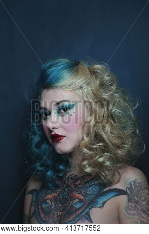 Portrait of beautiful tattooed young woman with fancy makeup and hairdo