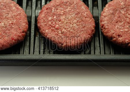 Seasoned Beef Burgers With A Pinch Of Salt And Black Pepper On The Grill