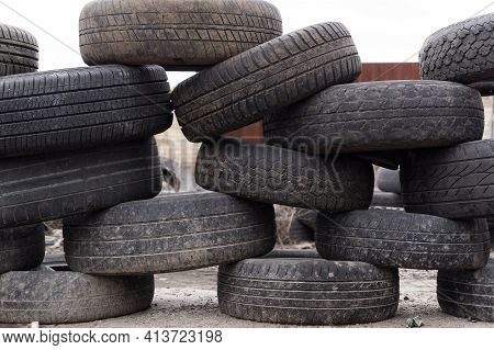 A Wall Of Spoiled Wheels. Fencing Made Of Old Tires For Car Wheels. Dump Of Wheels. Daylight.