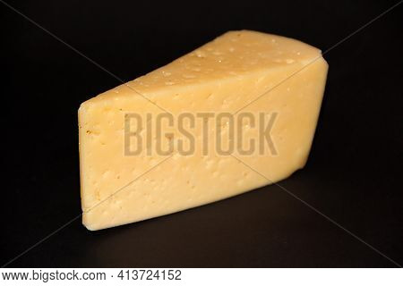 Piece Of Hard Cheese On Black Background. Fresh Cheese On Dark Background. Food Ingredient. Appetizi