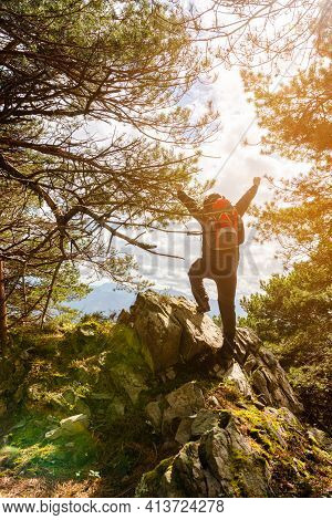 Hiker With Backpack Reaches The Summit In The Forest Of A Mountain Peak. Success Freedom And Happine