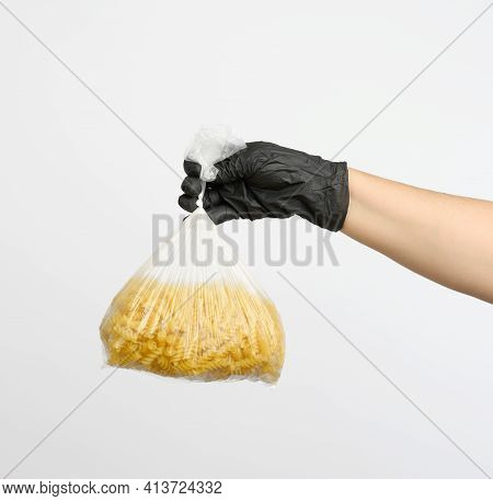 Female Hand In A Black Glove Holds A Transparent Bag With Raw Fusilli Pasta On A White Background