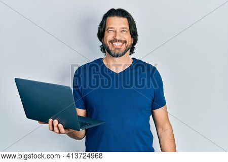 Middle age caucasian man working using computer laptop looking positive and happy standing and smiling with a confident smile showing teeth