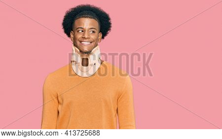 African american man with afro hair wearing cervical neck collar smiling looking to the side and staring away thinking.
