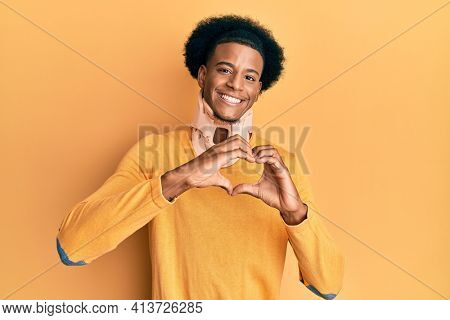 African american man with afro hair wearing cervical neck collar smiling in love showing heart symbol and shape with hands. romantic concept.