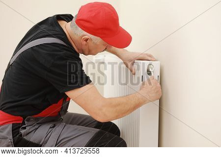 Man In Work Overalls Using Wrench While Installing Heating Radiator In Room. Plumber Installing Heat