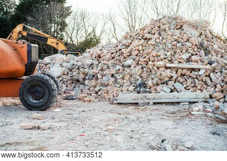 Excavator Removes Construction Waste After Building Demolition. Building Rubble, Bricks, Stones. Jun