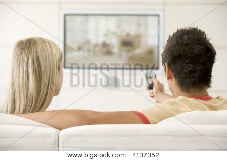 Couples In Living Room Watching Television