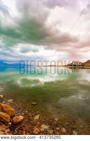 The smooth surface of the salty sea reflects the sky and clouds. Israel, legendary Dead Sea. Low winter clouds are reflected in the green water.