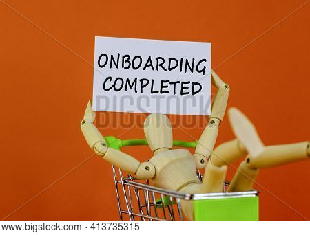 Onboarding Completed Symbol. White Paper. Words 'onboarding Completed'. Wooden Model Of A Human In A