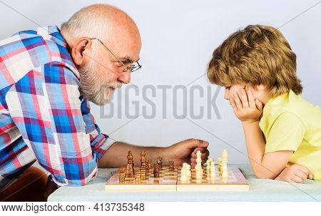 Grandfather And Grandson Playing Chess. Child Learning To Play Chess. Little Boy Think Or Plan Chess