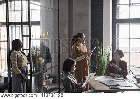 Multi-ethnic Group Of Elegant Businesswomen Working Together In Graphic Office Interior, Copy Space