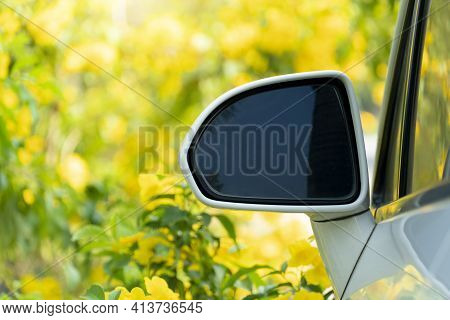Close-up Edge Of The Side Mirror Car White Color. And Bright Yellow Trumpet Shaped Or Bignoniaceae F