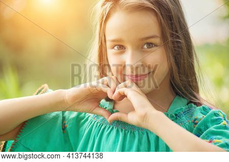 Cute child, little girl showing heart gesture and smiling outdoor. Love summer. Beautiful seven years old child enjoying nature outdoors. Healthy carefree kid playing outside in a park