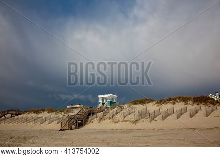 The beach at the Outer Banks of North Carolina has an eerie feeling when the storm clouds come through.  This is a popular travel vacation destination.  The waterfront has dunes to prevent erosion.