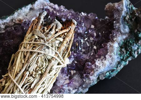 A Close Up Image Of A White Sage Smudge Bundle And Amethyst Crystal On A Black Background.